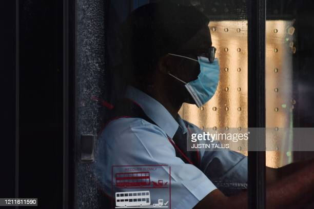 A bus driver wears a face mask as a precaution as he drives a bus on Oxford Street in London on May 2 as life in Britain continues during the...