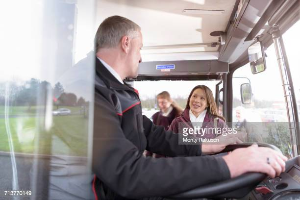 Bus driver with passengers boarding electric bus