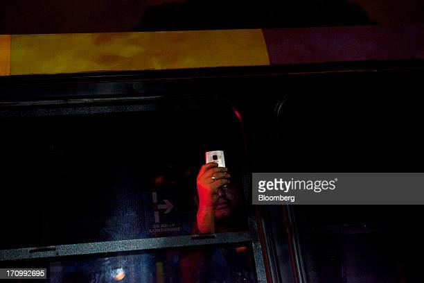 A bus driver's assistant takes photographs with a mobile phone from a stranded bus during demonstrations in downtown Rio de Janeiro Brazil on...