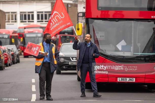 Bus drivers wave flags and hold placards during a strike involving bus drivers employed by three subsidiaries of RATP, at Shepard's Bus Garage in...