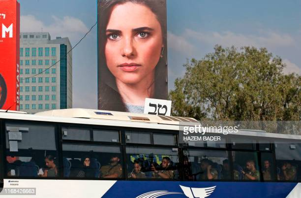 A bus drives below an electoral billboard with the portrait of Ayelet Shaked chairwoman of Israel's United Right party in the southern city of...