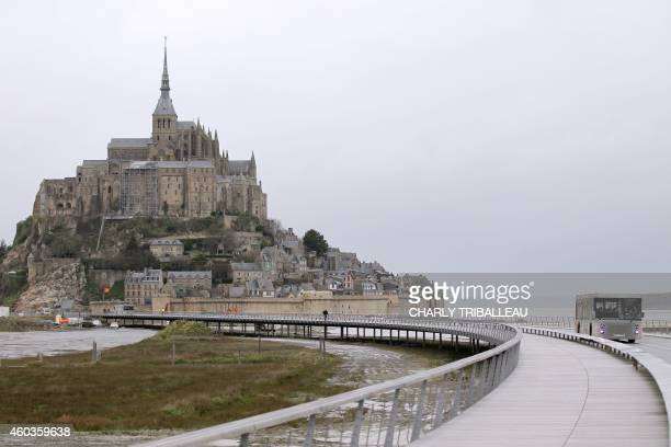 A bus drives for the first day on the new footbridge connecting the mainland to the MontSaintMichel northwestern France on December 12 2014 The...