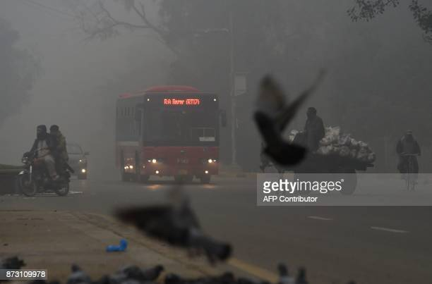 A bus drives on a street amid heavy smog in Lahore on November 12 2017 Large swathes of Pakistan and north India see a spike in pollution at the...