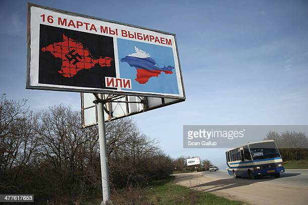 A bus drives past a billboard that reads 'On March 16 we will choose' and shows a map of Crimea with a swastika 'or' a map of Crimea with the colours...