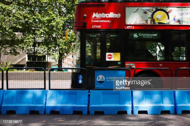 Bus drives past a section of roadway newly assigned for cyclists and pedestrians, part of the Mayor of London's 'Streetspace' scheme, on Park Lane in...