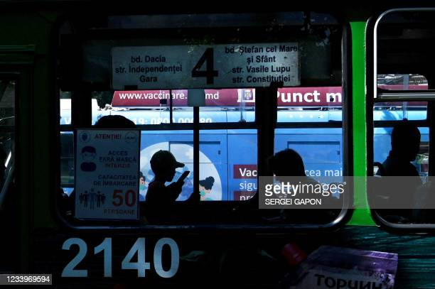 Bus drives past a trolleybus equipped with a vaccination station in central Chisinau on July 12 amid the ongoing Covid-19 pandemic. - The mobile...