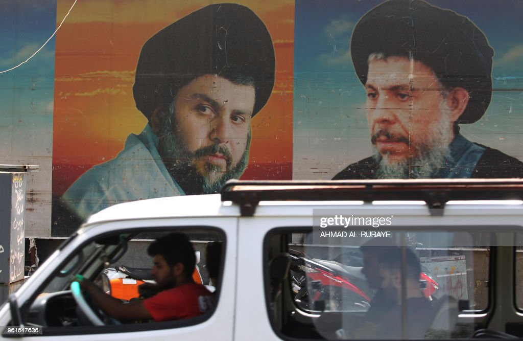 A bus drives past on a poster of Shiite cleric Moqtada Sadr in Sadr City, east of the Iraqi capital Baghdad on May 23, 2018. - Sadr -- whose fighters were once accused of sectarian killings -- has reinvented himself as an anti-graft crusader looking to bridge Iraqi society in alliance with secular leftists.