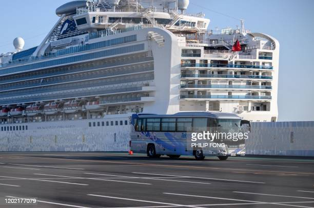 A bus drives through dockside past the Diamond Princess cruise ship in quarantine due to fears of new COVID19 coronavirus at Daikoku pier cruise...
