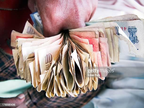 Bus fare collector holds the bills from passengers between his fingers to exchange.