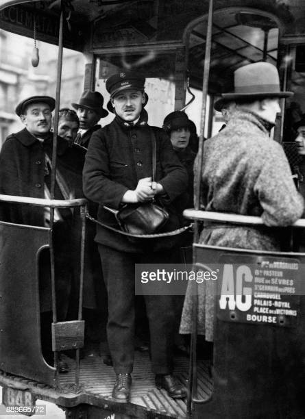 A bus inspector stands at the back of the bus in 1926 in Paris / AFP PHOTO /
