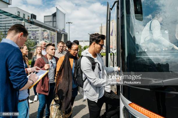 bus is boarded by travellers, ready to start their journey. - coach bus stock photos and pictures