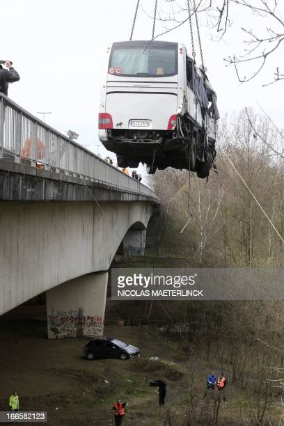 Bus is hoisted up after it crashed off the E34 highway near Ranst, Antwerp province, on April 14, 2013. At least five people died and several were...