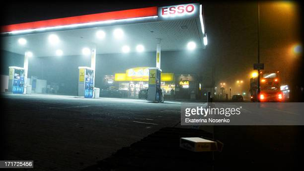 Bus is passing by the empty petrol station on a foggy night at the suburbs of London.