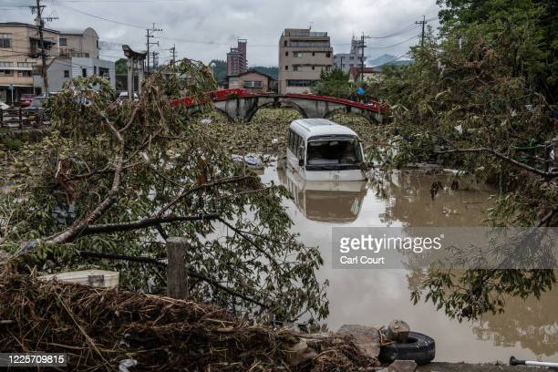 Bus lies in a pond next to a damaged bridge after torrential rain caused the nearby Kuma River to burst its banks and flood the area, on July 9, 2020...
