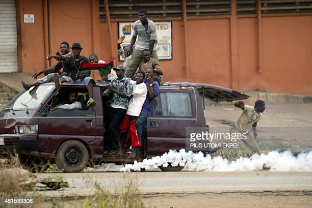 A bus load of members of the banned Movement for the Actualisation of the Sovereign State of Biafra drives past police with a Biafran flag in Onitsha...