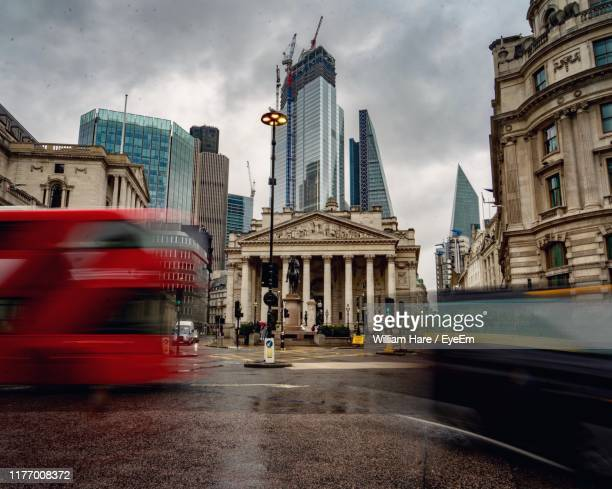 bus moving on road against sky in city - bank of england stock pictures, royalty-free photos & images