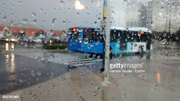 Bus Moving On Street Seen From Wet Glass Window