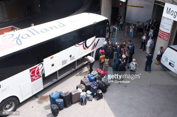 A bus of Haitian asylum seekers from the United States arrives at the Olympic Stadium in Montreal Quebec on August 3 2017 / AFP PHOTO / Catherine...