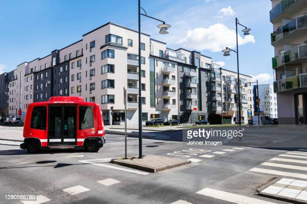 bus on road, blocks of flats on background - autonomous technology stock pictures, royalty-free photos & images