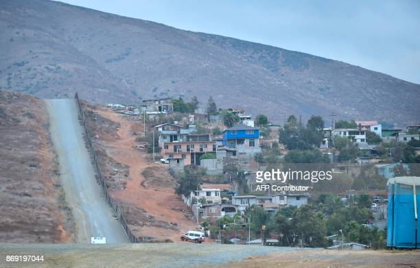 A bus on the Mexico side of the USMexico border makes its way up a winding dirt hill in Tijuana beside a fence seperating the two countries near...