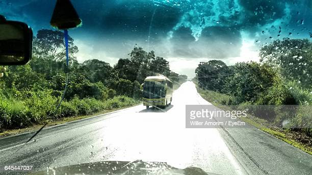 Bus On Wet Road Against Sky Seen Through Car Windshield