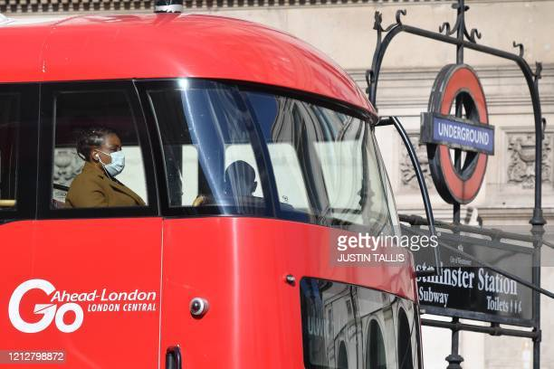 Bus passenger wears a face-mask in central London on May 12 during the novel coronavirus COVID-19 pandemic. - The British government on Monday...