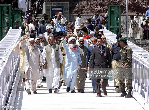 Bus passengers from Pakistani controlled Kashmir and Indian Kashmir wave as they walk with officials across Kaman Bridgethe defacto border between...