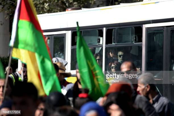Bus passengers stare the march as Kurdish people living in Greece shout slogans against Turkish president Recep Tayyip Erdogan as they stage a...
