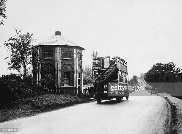 A bus passes by the Round House an octagonal former toll house at Brook Street Hill near Brentwood in Essex 14th August 1925