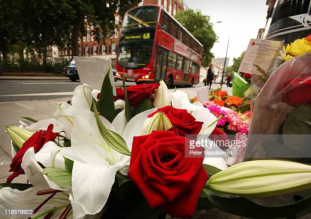 A bus passes floral tributes placed next to a memorial remembering the victims of the London bus bombing 7/7 terrorist attacks on July 7 2011 in...