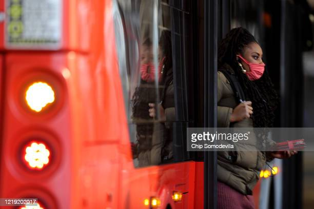 Bus riders wear mandatory face coverings in an effort to prevent the spread of the novel coronavirus at the Sarbanes Transit Center April 16 2020 in...