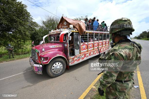 Bus rides past soldiers standing guard near a barricade blocking the Panamerican highway after a protest against the government triggered by a now...