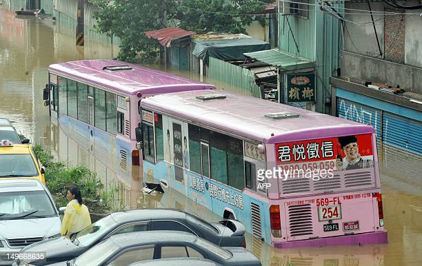 A bus sits half submerged on a flooded road in New Taipei City on August 2 2012 Typhoon Saola pounded Taiwan with fierce winds and torrential rain...