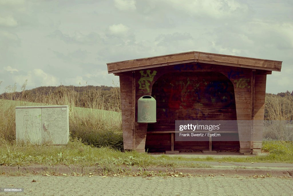 Bus Stand By Street Against Cloudy Sky : Stock-Foto