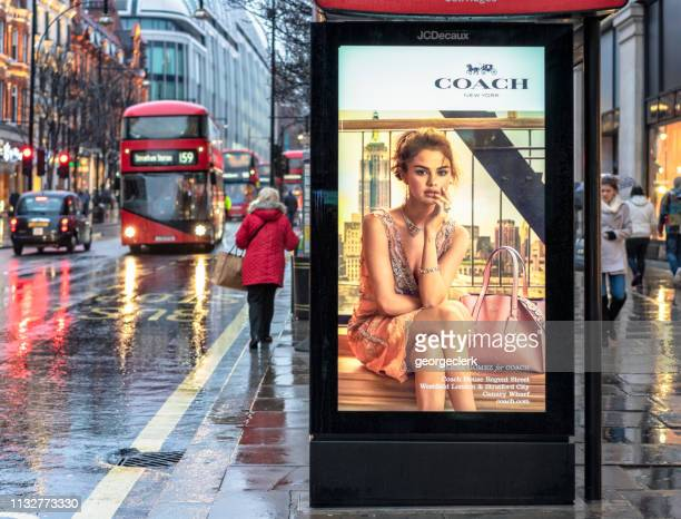 bus stop advertisement on rainy london street - advertising_campaign stock pictures, royalty-free photos & images