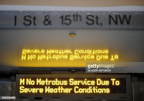 A bus stop electronic board informs commuters about the interrupted service during a snowstorm in downtown Washington DC on January 22 2016 A monster...