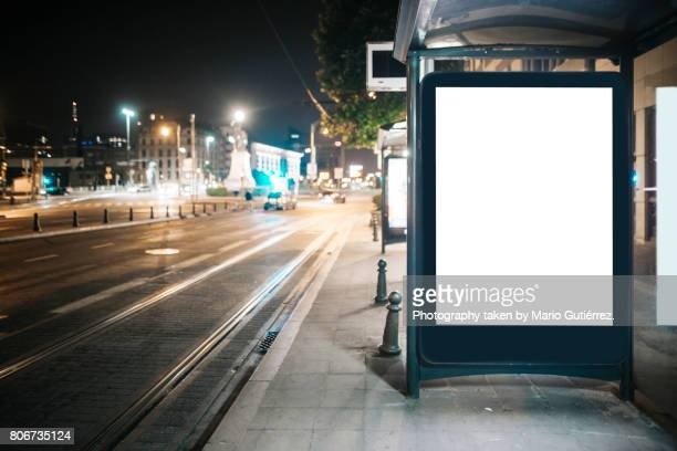 bus stop with billboard at night - licht stock-fotos und bilder