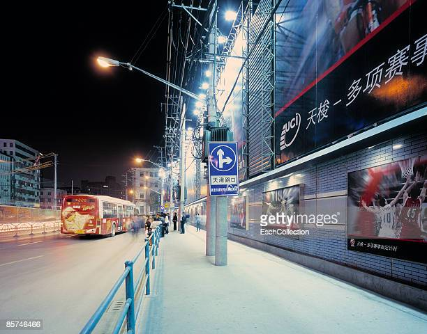 Bus stop with people and large billboard at night.