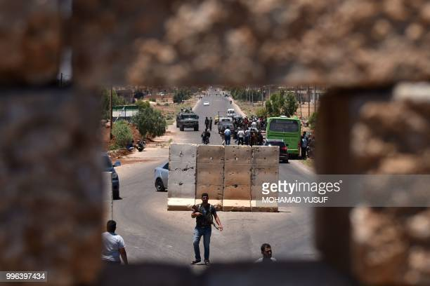 Bus stops at a checkpoint as displaced Syrians from the Daraa province come back to their hometown in Bosra, southwestern Syria, on July 11, 2018. -...