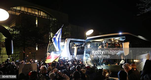 A bus Syrian migrants from German Bavarian town of Landshut arrives on January 14 2016 in front of the Chancellory in Berlin A German small town...