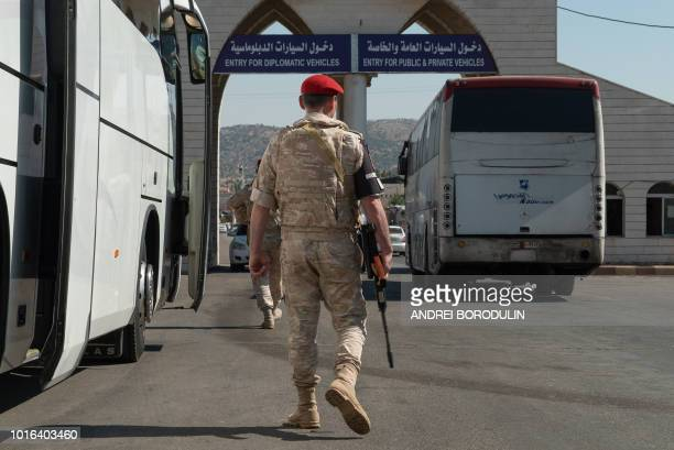 A bus transporting Syrian refugees back from Lebanon is seen on the border between Syria and Lebanon on August 13 2018 in Jdaidat Yabous during a...