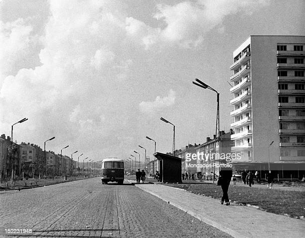 A bus travelling along an unsurfaced road in the Lenin quarter By the sides of the road is a series of buildings Sofia November 1961