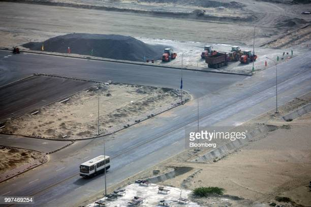 A bus travels along a road past a development site operated by China Overseas Ports Holding Co near Gwadar Port in Gwadar Balochistan Pakistan on...