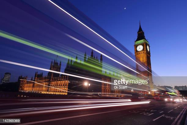 A bus travels along Westminster Bridge past the Houses of Parliament on March 27 2012 in London England