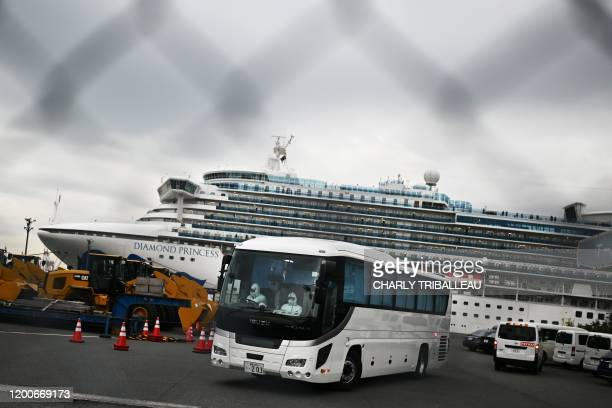 TOPSHOT A bus with a driver wearing protective gear departs from the dockside next to the Diamond Princess cruise ship which has around 3600 people...