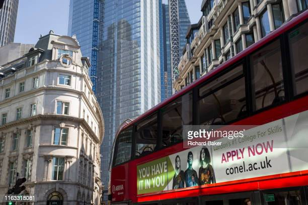 Bus with an ad for an educational college passes through the in the City of London, the capital's financial district , on 22nd August 2019, in...