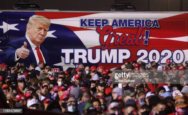 Bus with an image of U.S. President Donald Trump sits next to the crowd during a campaign rally at Richard B. Russell Airport on November 01, 2020 in...