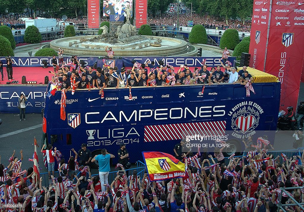 A bus with Atletico de Madrid football team celebrating their Spanish league title arrives at Neptuno square, in Madrid on May 18, 2014. Atletico Madrid claimed their 10th Spanish league crown on May 17, 2014 but first in 18 years after coming from behind to draw 1-1 away at title rivals Barcelona.