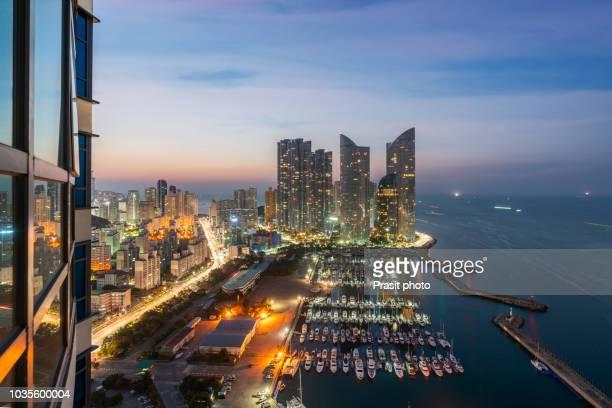 busan city skyline view at haeundae district, gwangalli beach with yacht pier at busan, south korea. - busan stock pictures, royalty-free photos & images