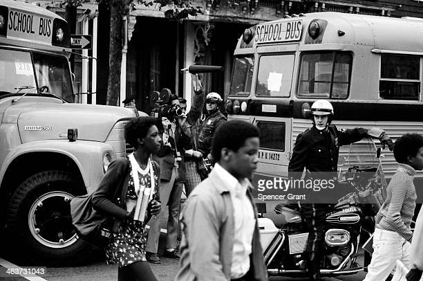 Bused black schoolchildren arrive with police escort at South Boston High School during courtordered desegregation crisis South Boston Massachusetts...